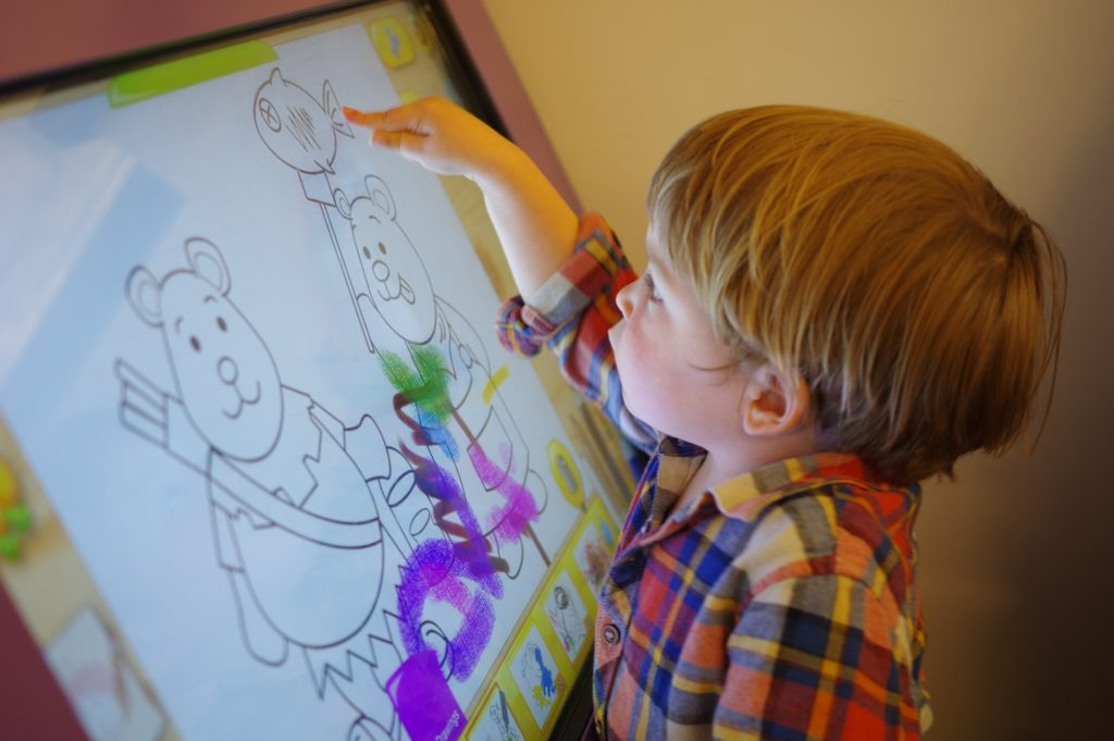 Child colouring on tablet at nursery