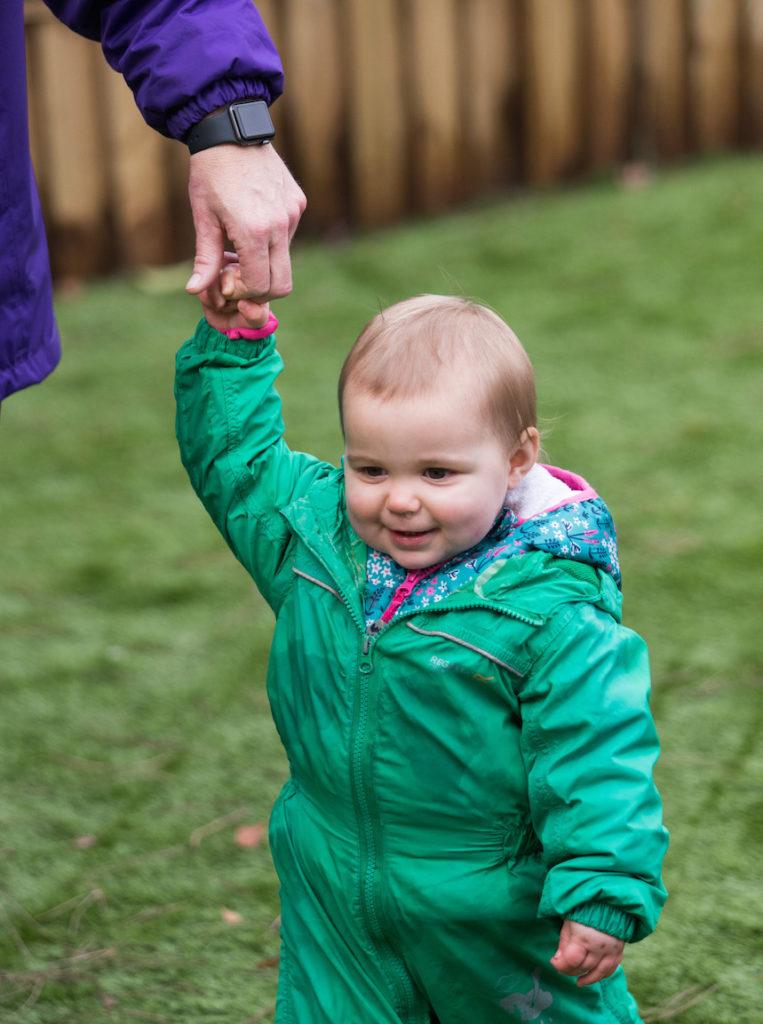 Child being walked by nursery staff